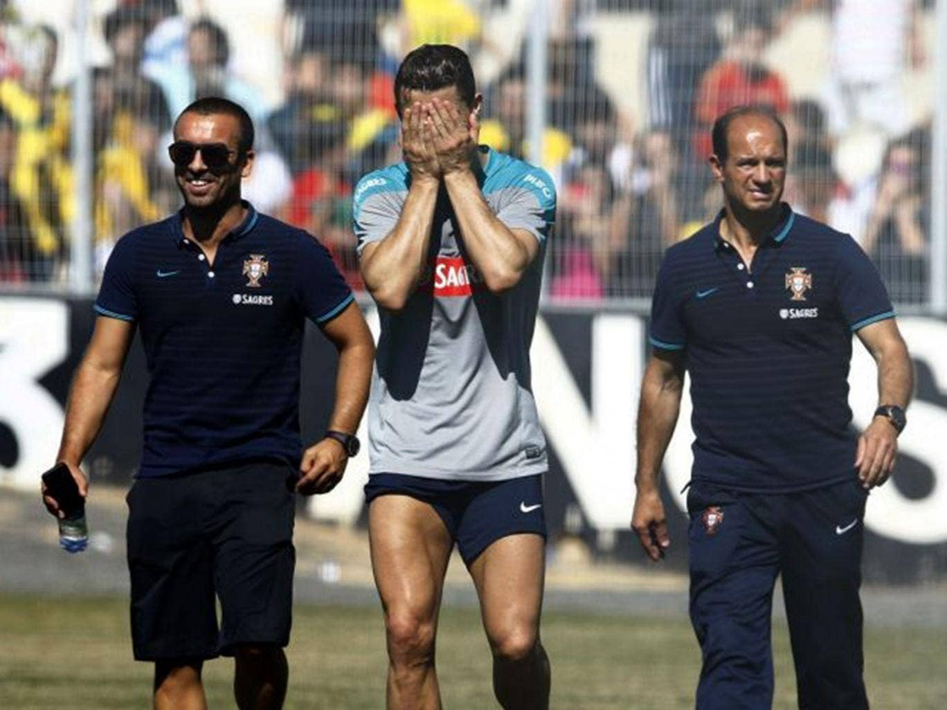 Cristiano Ronaldo covers his face as he limps out of a Portugal training session
