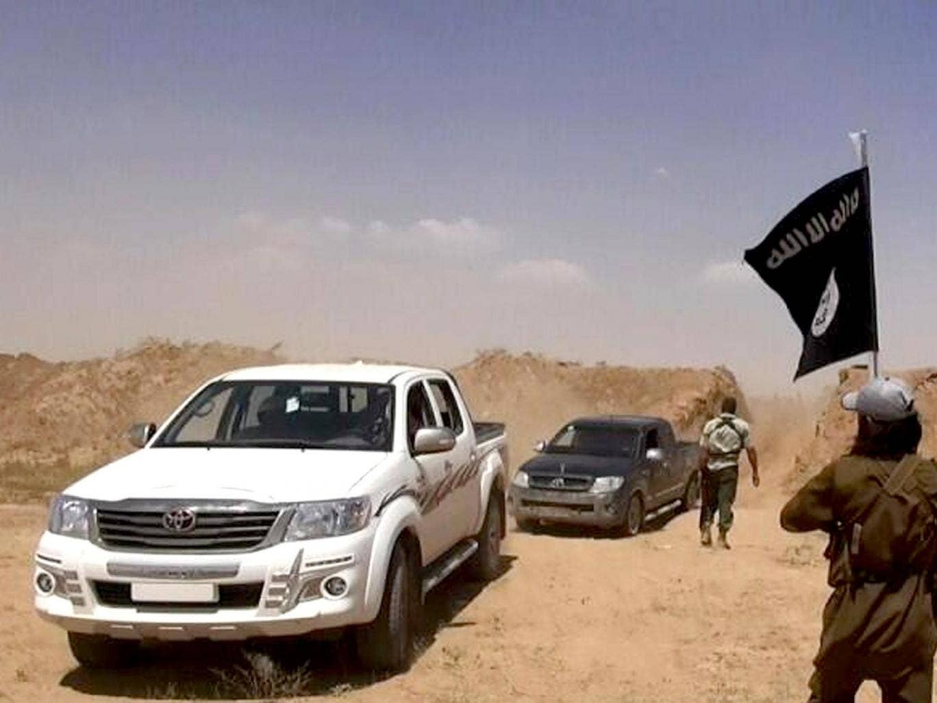 Militants from the Islamic State of Iraq and the Levant (ISIL) remove part of the soil barrier on the Iraq-Syria borders and move through it