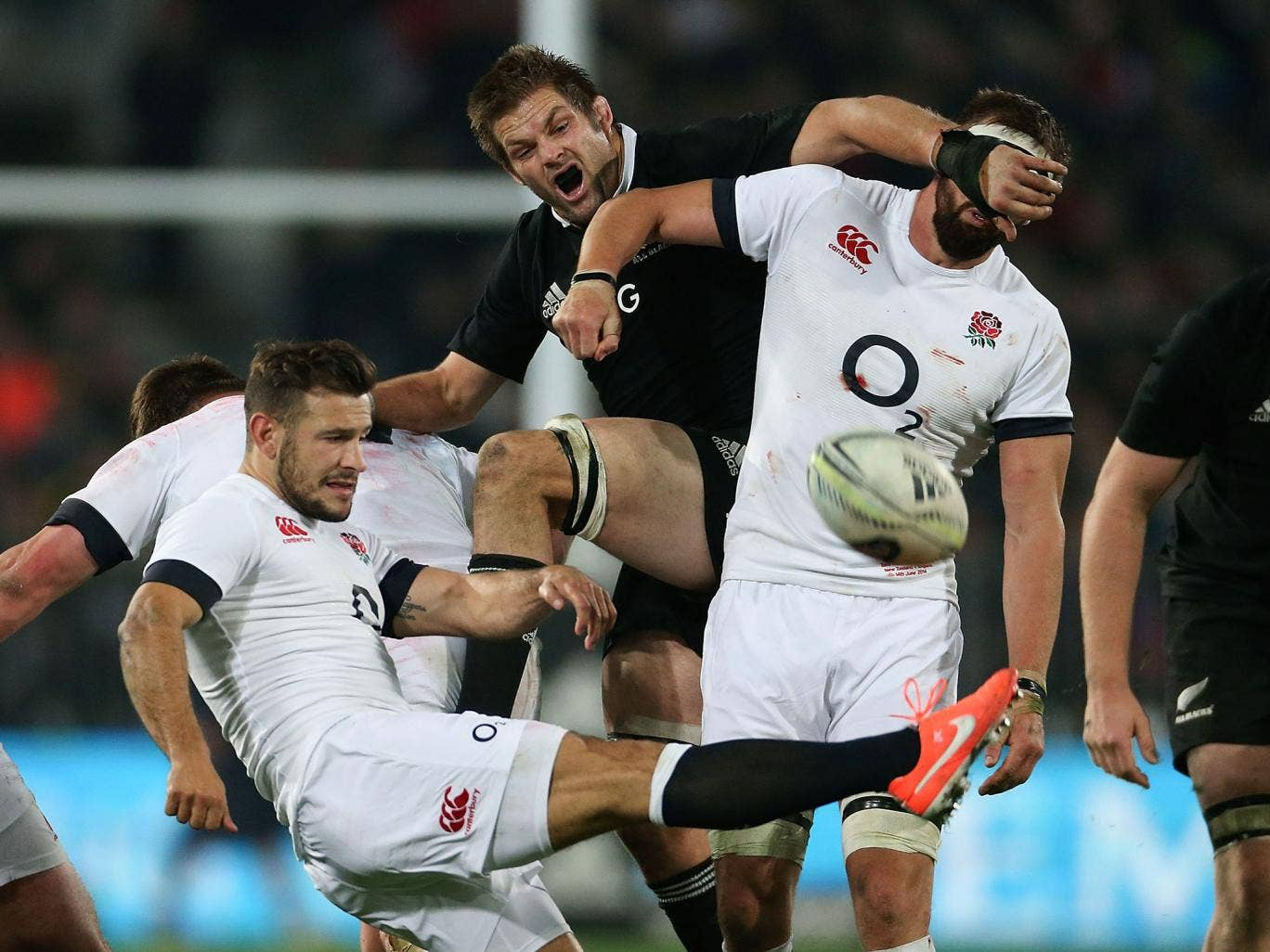 Danny Care kicks the ball as Richie McCaw attempts to push past Tom Wood