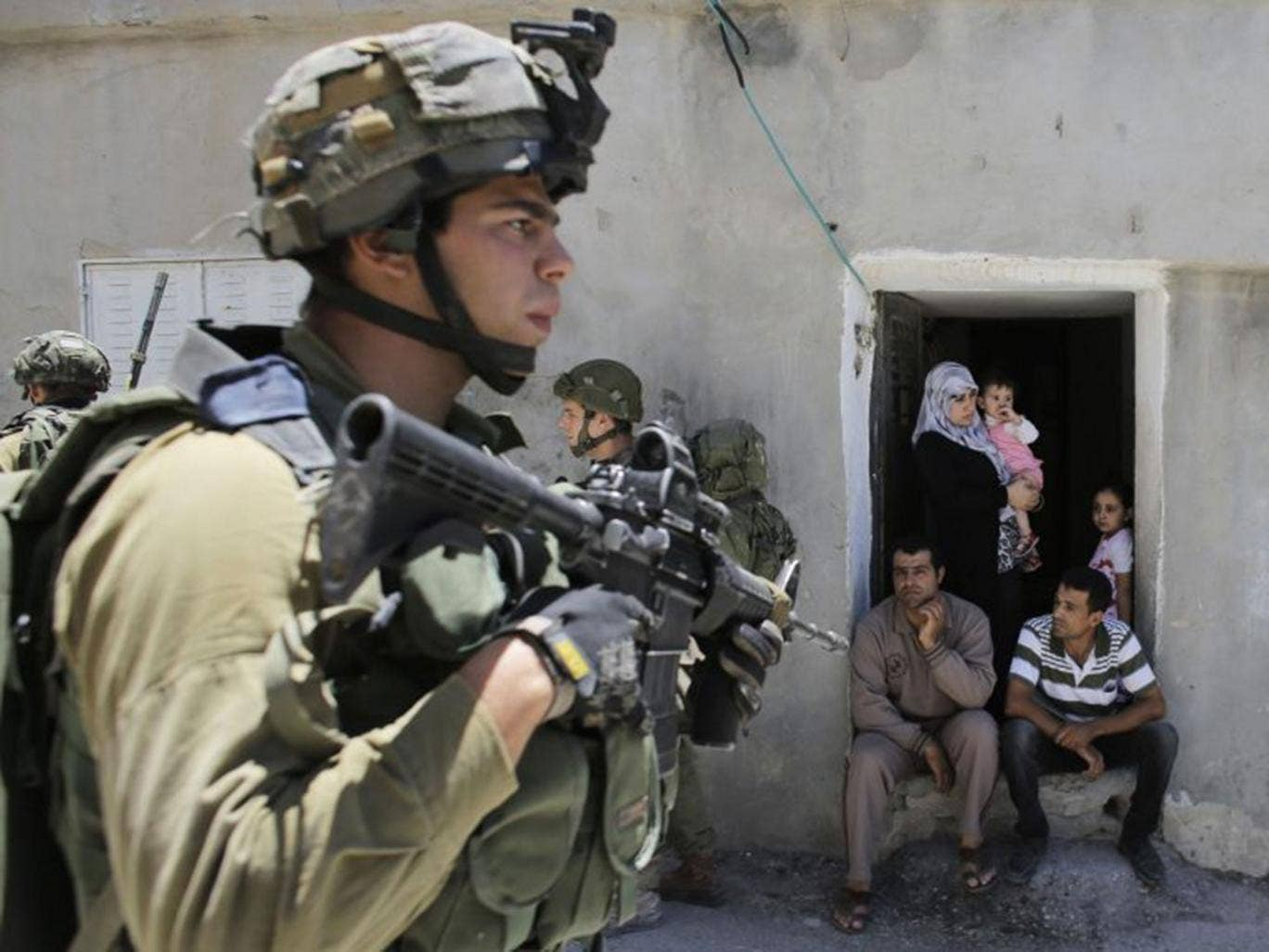 Palestinians watch Israeli soldiers patrol near the West Bank City of Hebron yesterday, close to where the teenagers were last seen