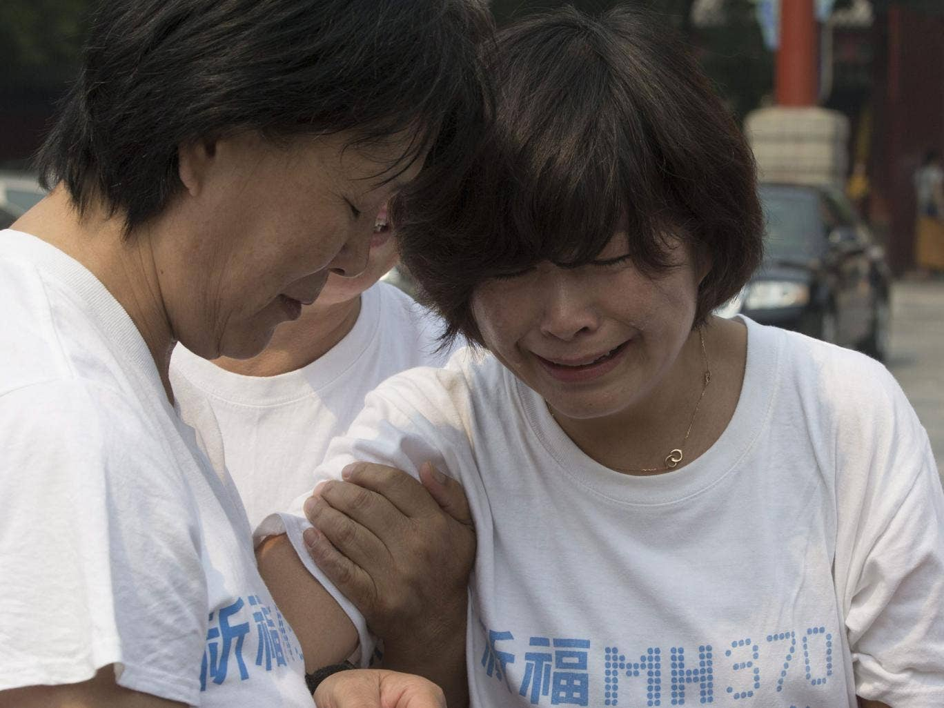 Chinese relatives of passengers of Malaysia Airlines flight MH370 console each other before entering the Lama Temple to pray in Beijing, China, 15 June 2014