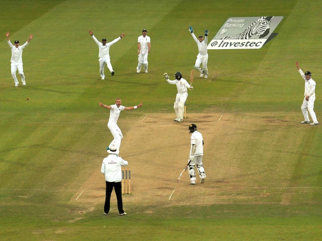 England players, led by paceman Stuart Broad, go up as one to appeal for the decisive wicket of Nuwan Pradeep at Lord's. But celebrations were cut short when the decision was quickly overturned by DRS