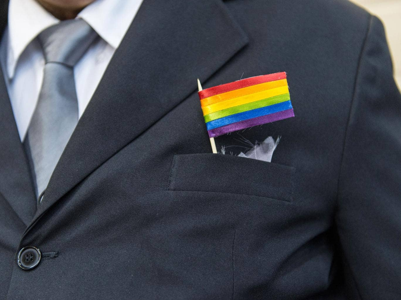 The father of a bride wears a rainbow flag during the wedding ceremony at the Court of Justice of the State of Rio de Janeiro in Rio de Janeiro, Brazil, on December 8, 2013. 130 gay couples are getting married in the first massive wedding ceremony since t