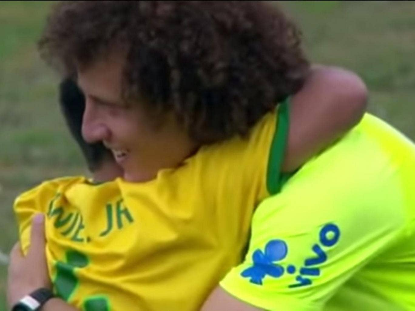 David Luiz embraces an eight-year-old Brazil fan after he ran on to the pitch at a training session