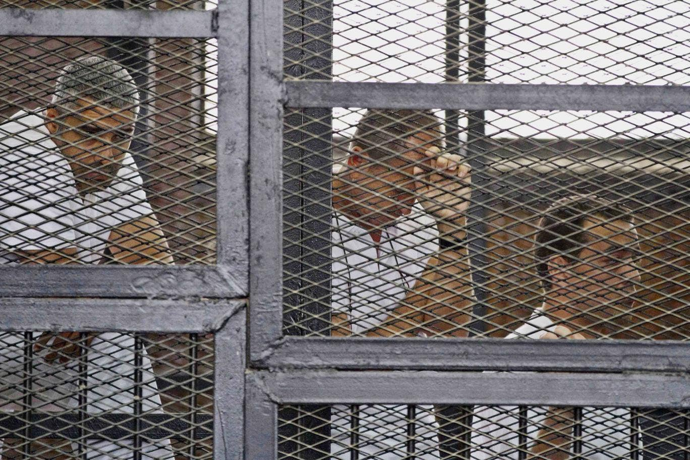 In this Thursday, May 15, 2014 file photo, from left, Mohammed Fahmy, Canadian-Egyptian acting bureau chief of Al-Jazeera, Australian correspondent Peter Greste, and Egyptian producer Baher Mohamed appear in a defendant's cage along with several other def