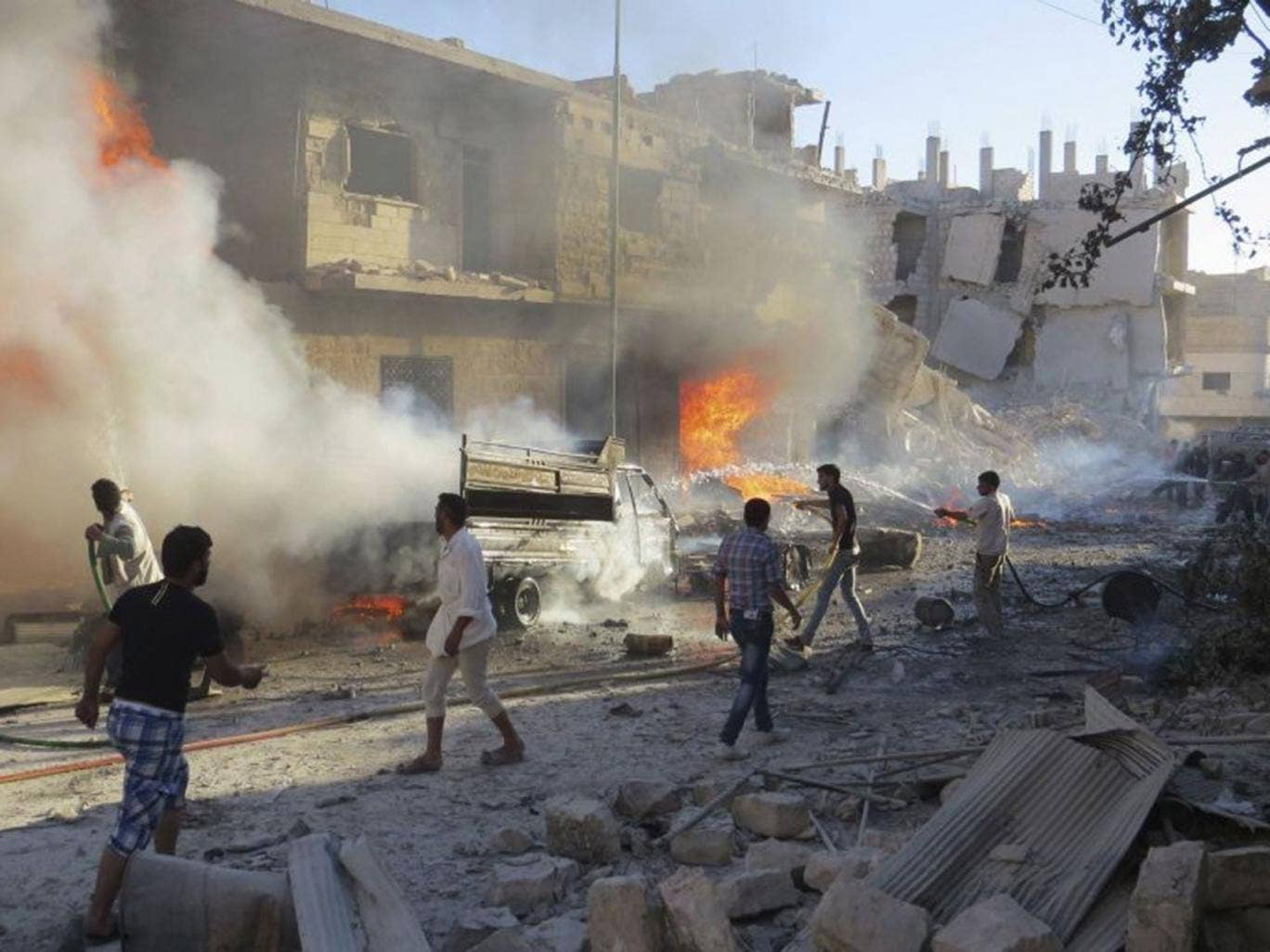 Men try to put out a fire at a site hit by what activists said was an airstrike by forces loyal to Assad, in Idlib on Sunday