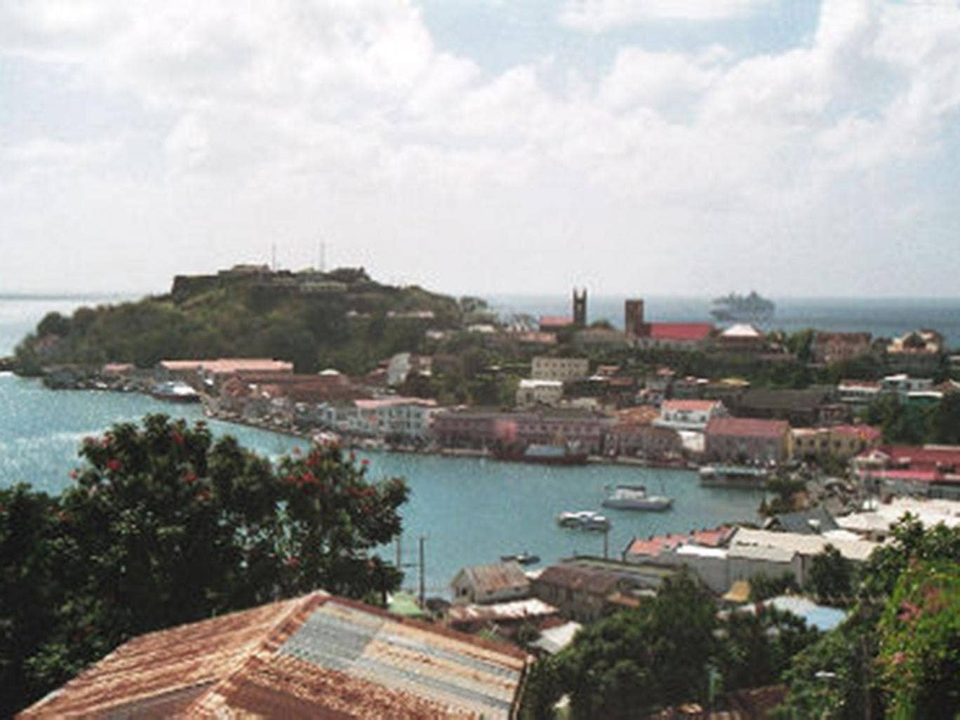 A British man has been arrested by police in the Caribbean over the death of his wife, after her body was found in a shallow grave on Grenada.