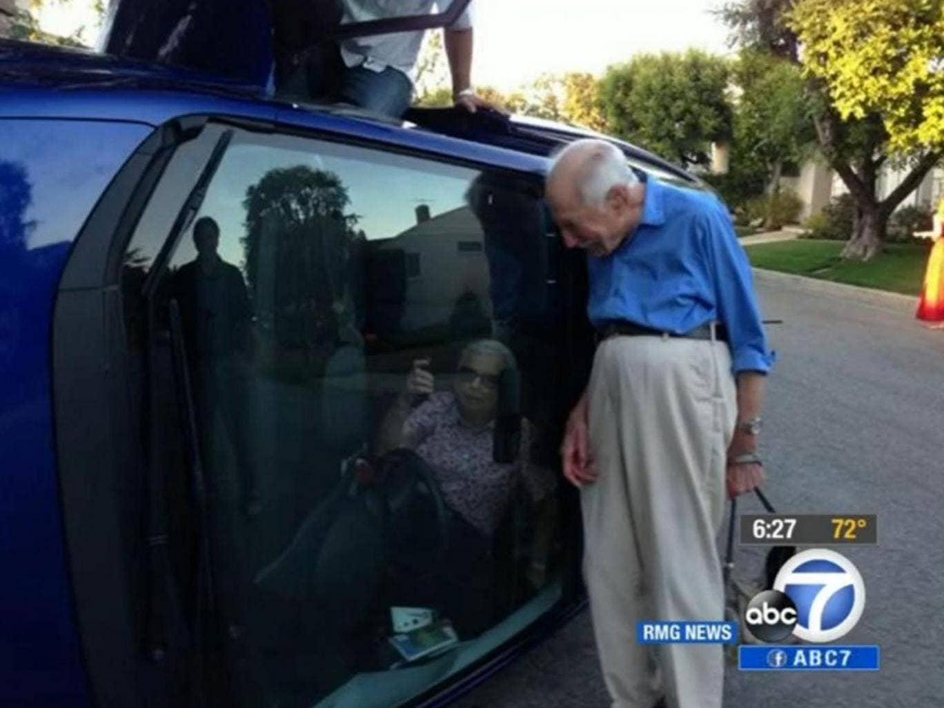 Benjamin Neufeld stood at the side of the car for pictures while his wife Elizabeth Neufeld asked for her purse so she could take pictures of herself while still trapped inside the car.