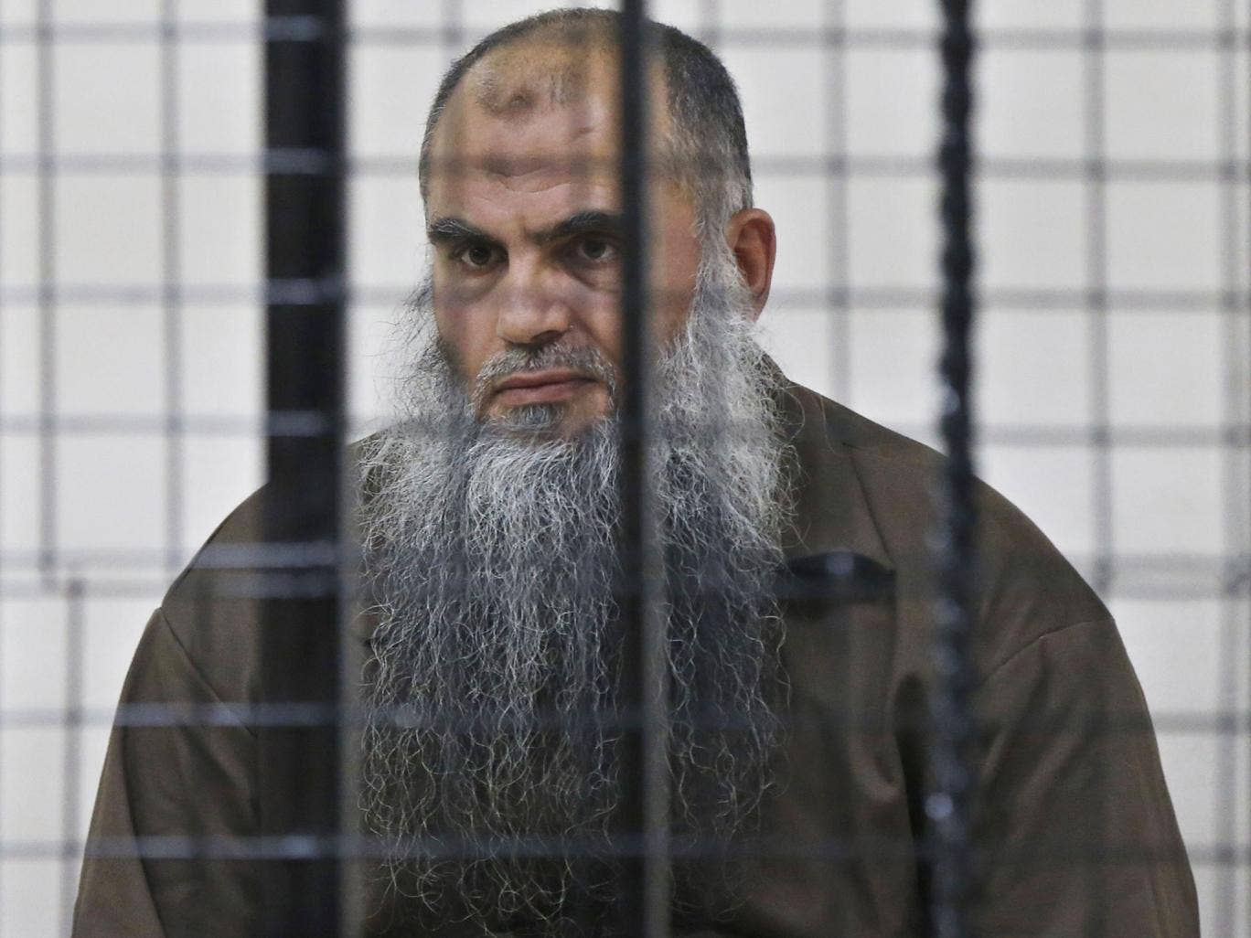 Radical Muslim cleric Abu Qatada looks on from behind bars at the State Security Court in Amman