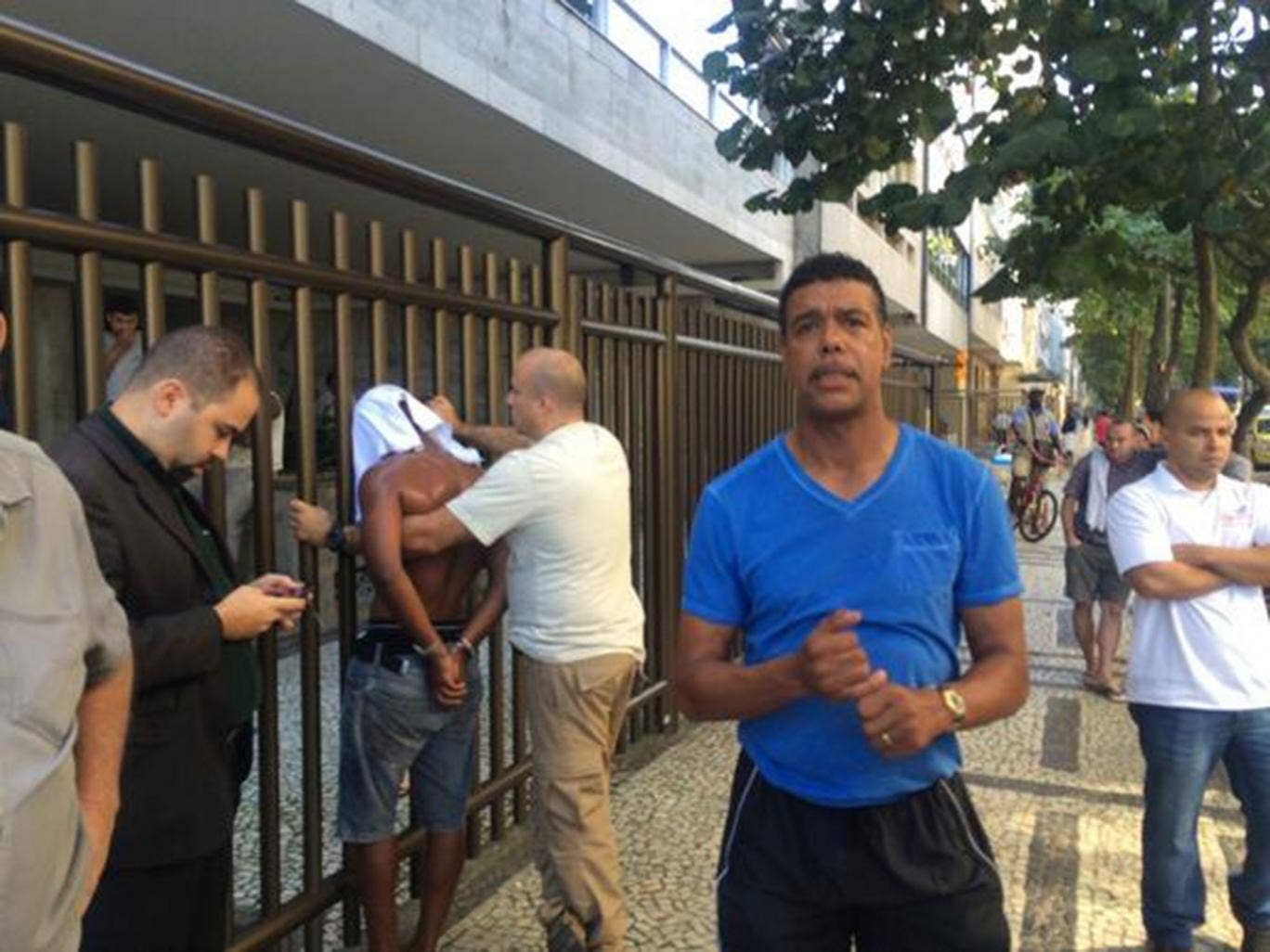 Chris Kamara poses in front of a robber that he chased and caught in Brazil