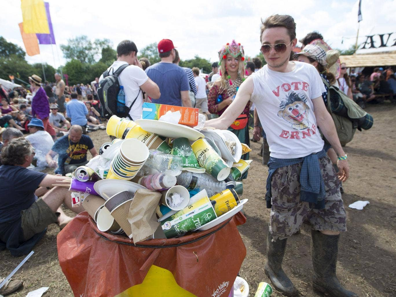 Festival goers use recycling bins at the Glastonbury Festival, at Worthy Farm in Somerset