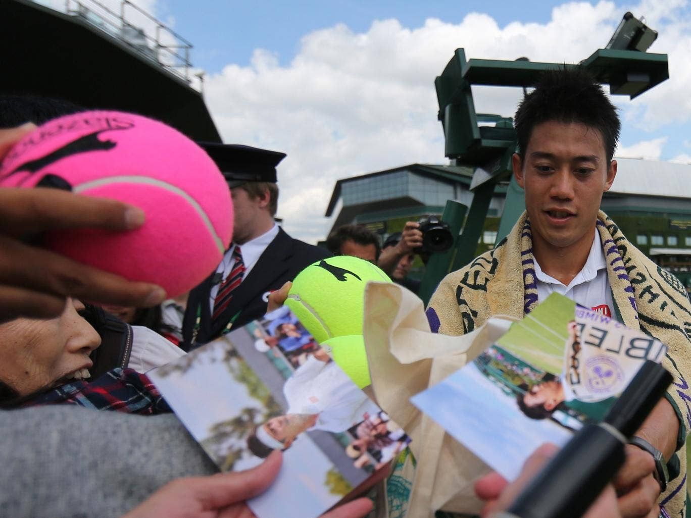 Japan's Kei Nishikori signs autographs after winning his men's singles third round match against Italy's Simon Bolelli