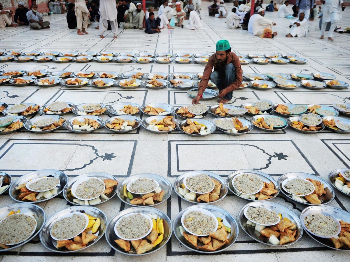 A Pakistani Muslim man arranges Iftar food for Muslim devotees