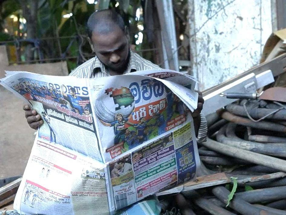 A man reading the special mosquito-repellent Mawbima paper