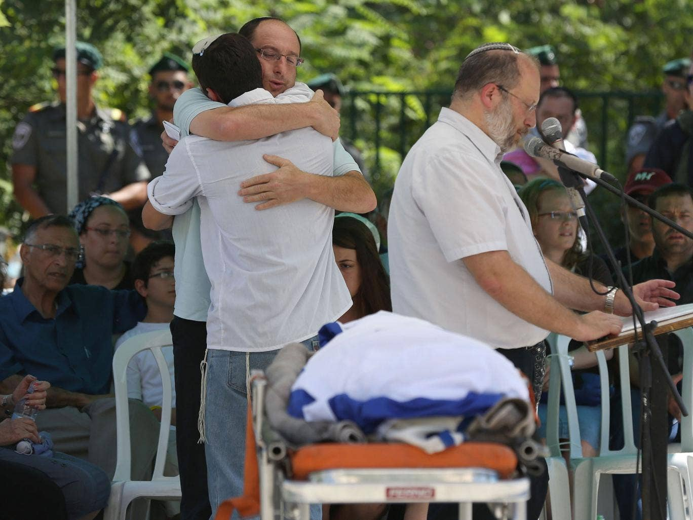 Ofir, the father of Gilad Shaer, 16, hugs a mourner as they stand in front of his son's body during a funeral service at his hometown, the Talmon Jewish settlement, near the West Bank city of Ramallah