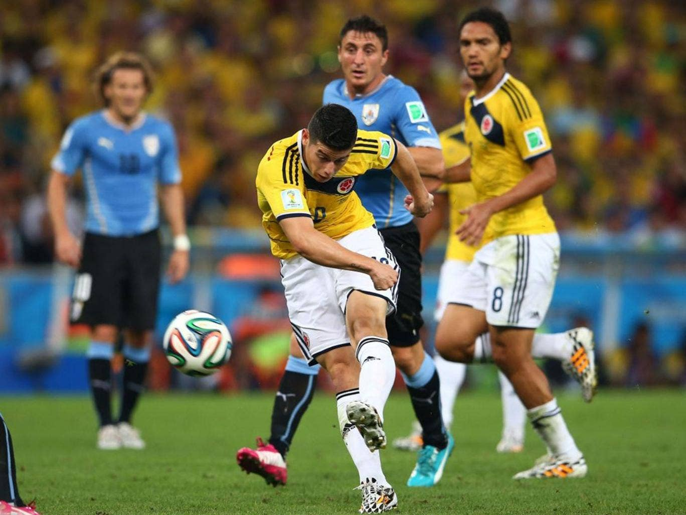 James Rodriguez shoots and scores his team's first goal during the 2014 FIFA World Cup Brazil round of 16 match between Colombia and Uruguay at Maracana on June 28, 2014