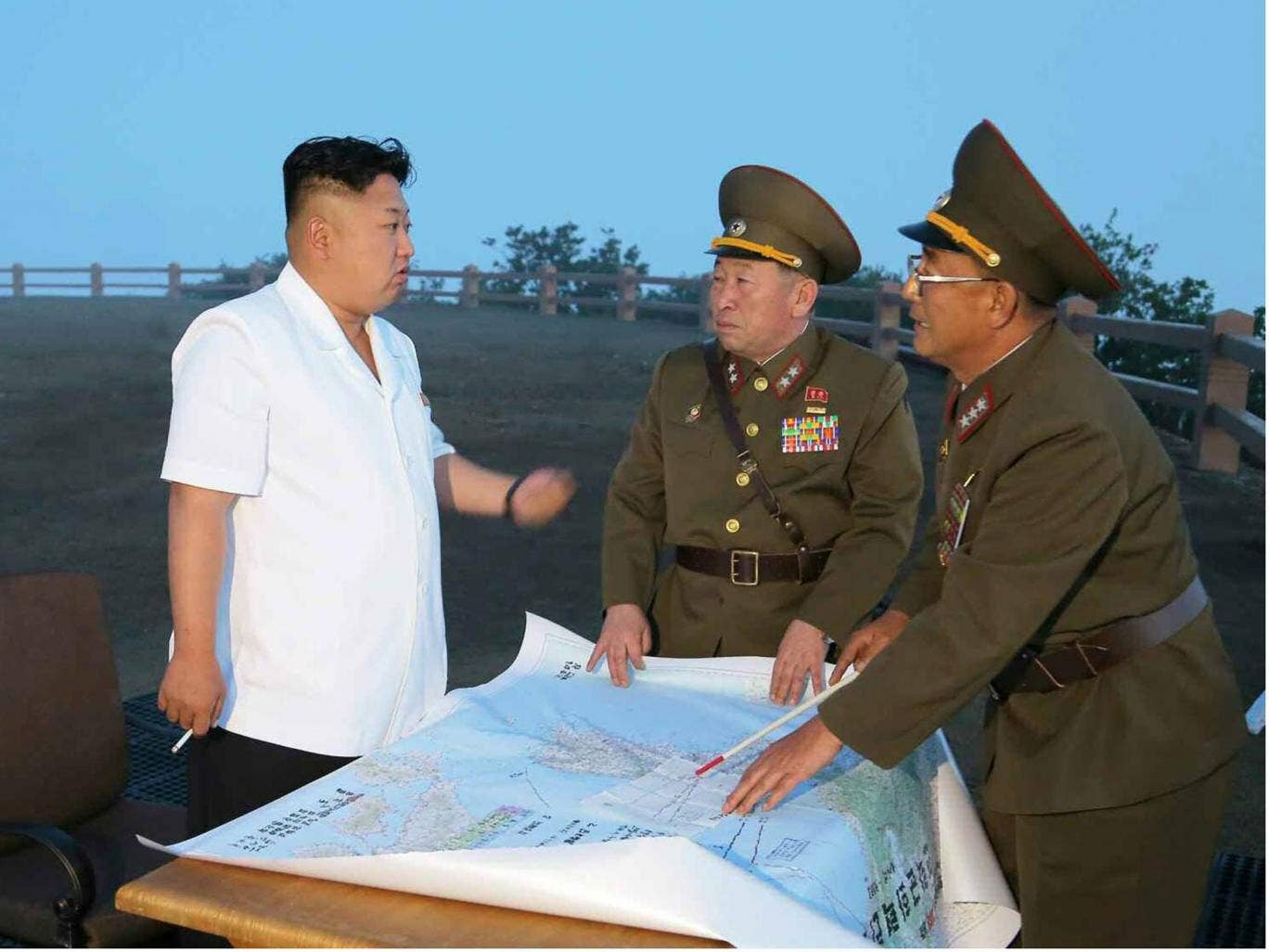Kim Jong-un talks to military officials during a tactical rocket firing drill of the North's Strategic Force