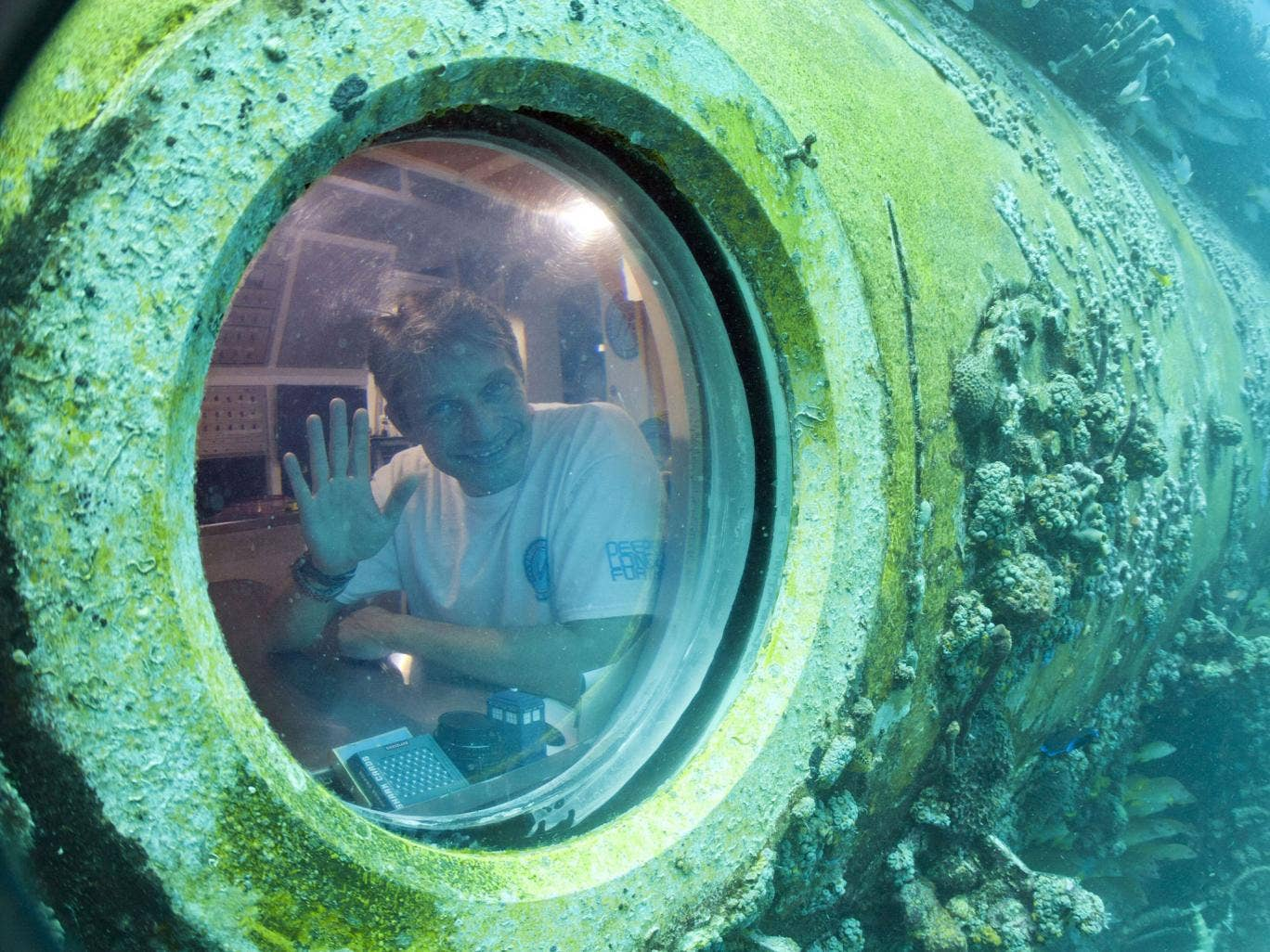 Fabien Cousteau waves from inside Aquarius Reef Base, a laboratory 63 feet below the surface in the waters off Key Largo, in the Florida Keys
