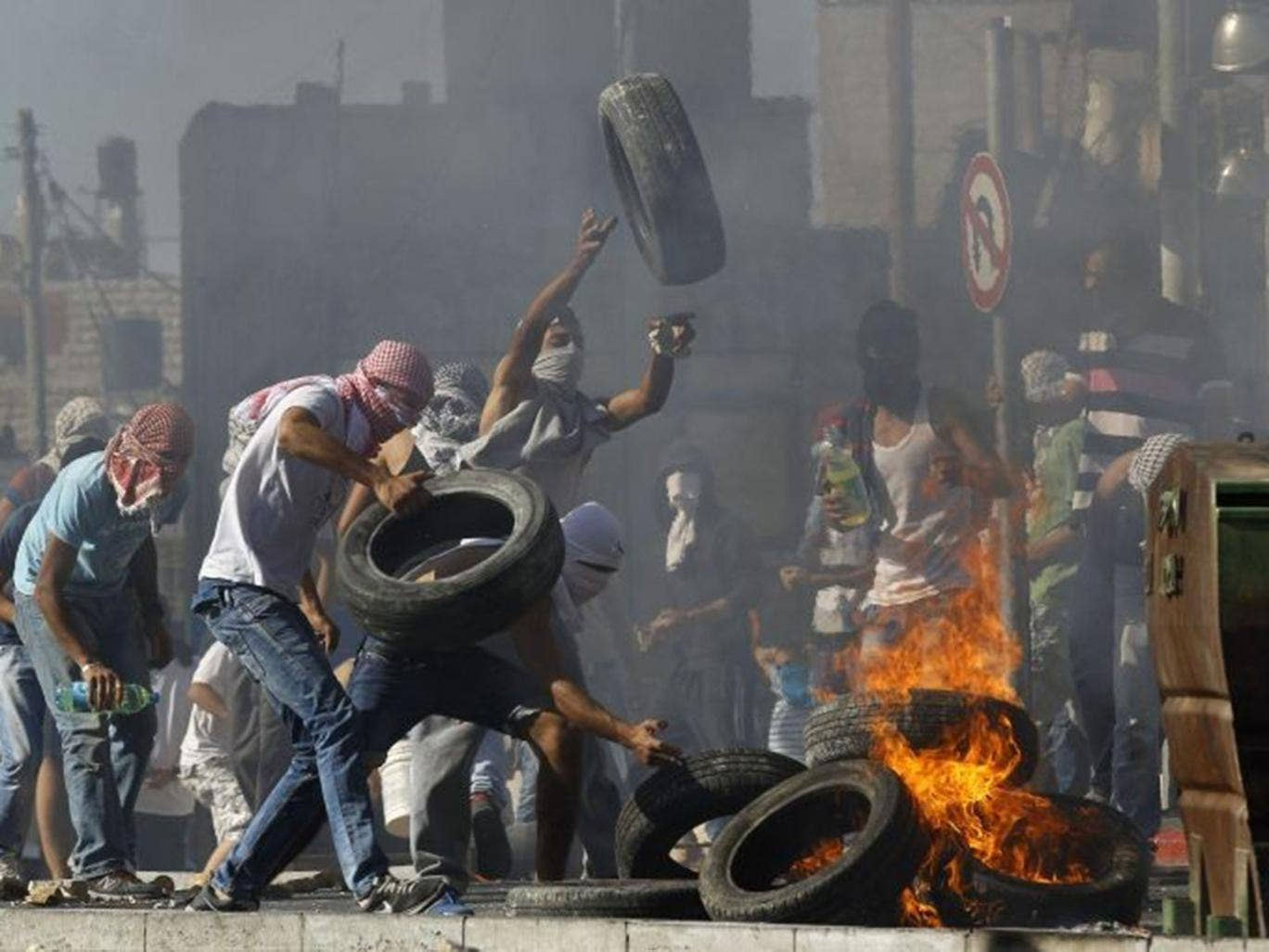 Palestinians set tyres ablaze during clashes with Israeli police in Shuafat, an Arab suburb of Jerusalem July 2, 2014.