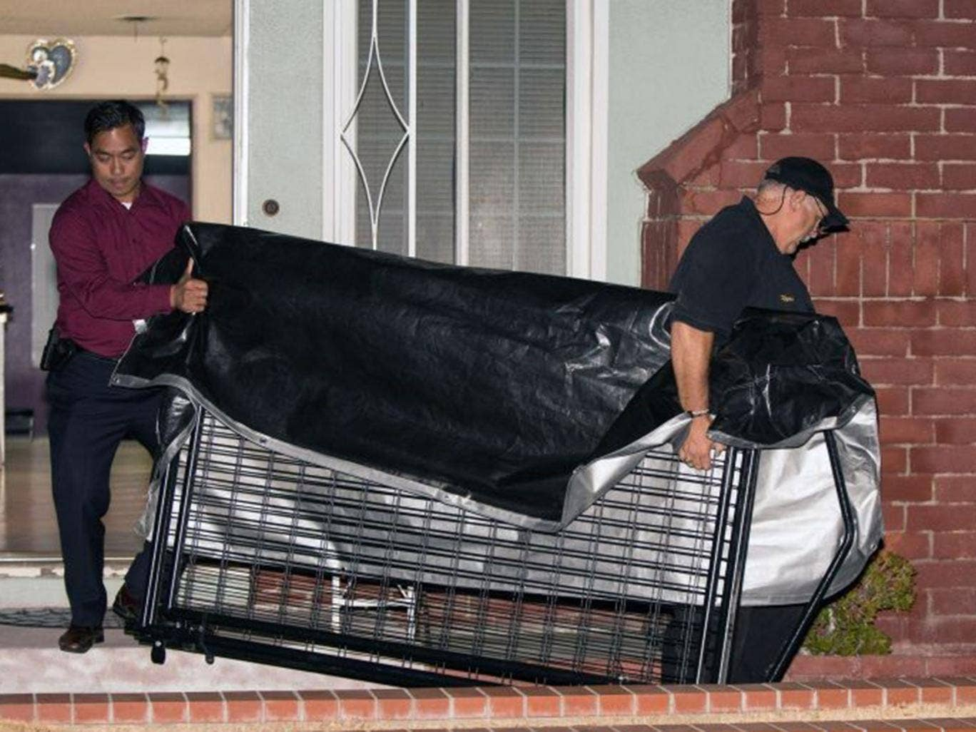 In this Tuesday, July 1, 2014 photo, a crime scene investigator and a detective carry a cage from a residence in Anaheim, Calif. An 11-year-old autistic boy who police suspect was kept in a cage has been removed from the home, and his parents have been ar