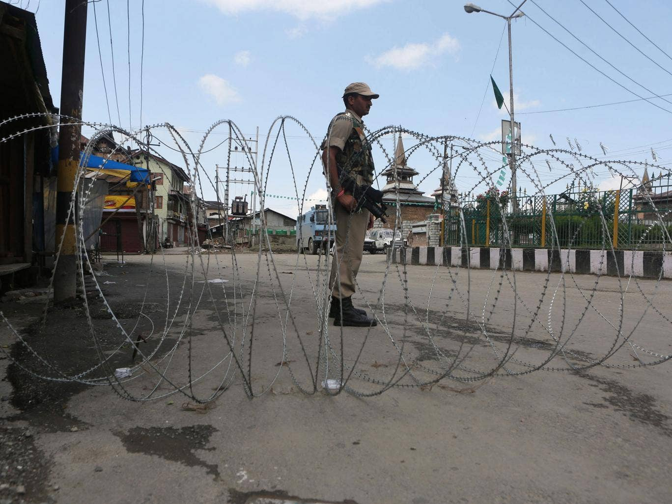 An Indian paramilitary soldier stands guard near barbed wire setup as barricade during restrictions in downtown area of Srinaga