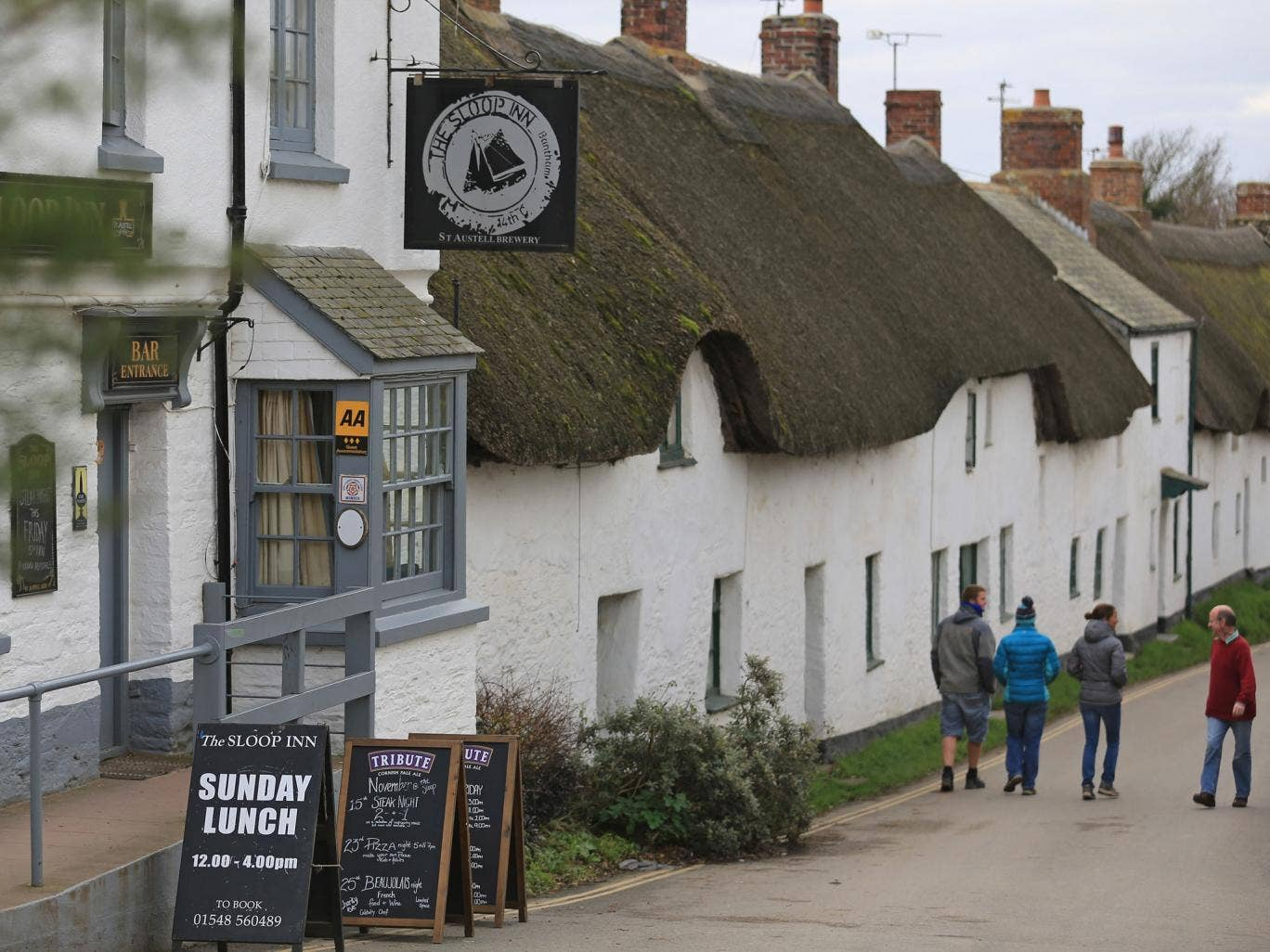 Caption:BANTHAM, ENGLAND - NOVEMBER 13: People walk past the local pub in the picturesque seaside village of Bantham on November 13, 2013 in Devon, England. Evans Estates, which has owned the land, buildings and popular surfing beach for nearly 100 years,