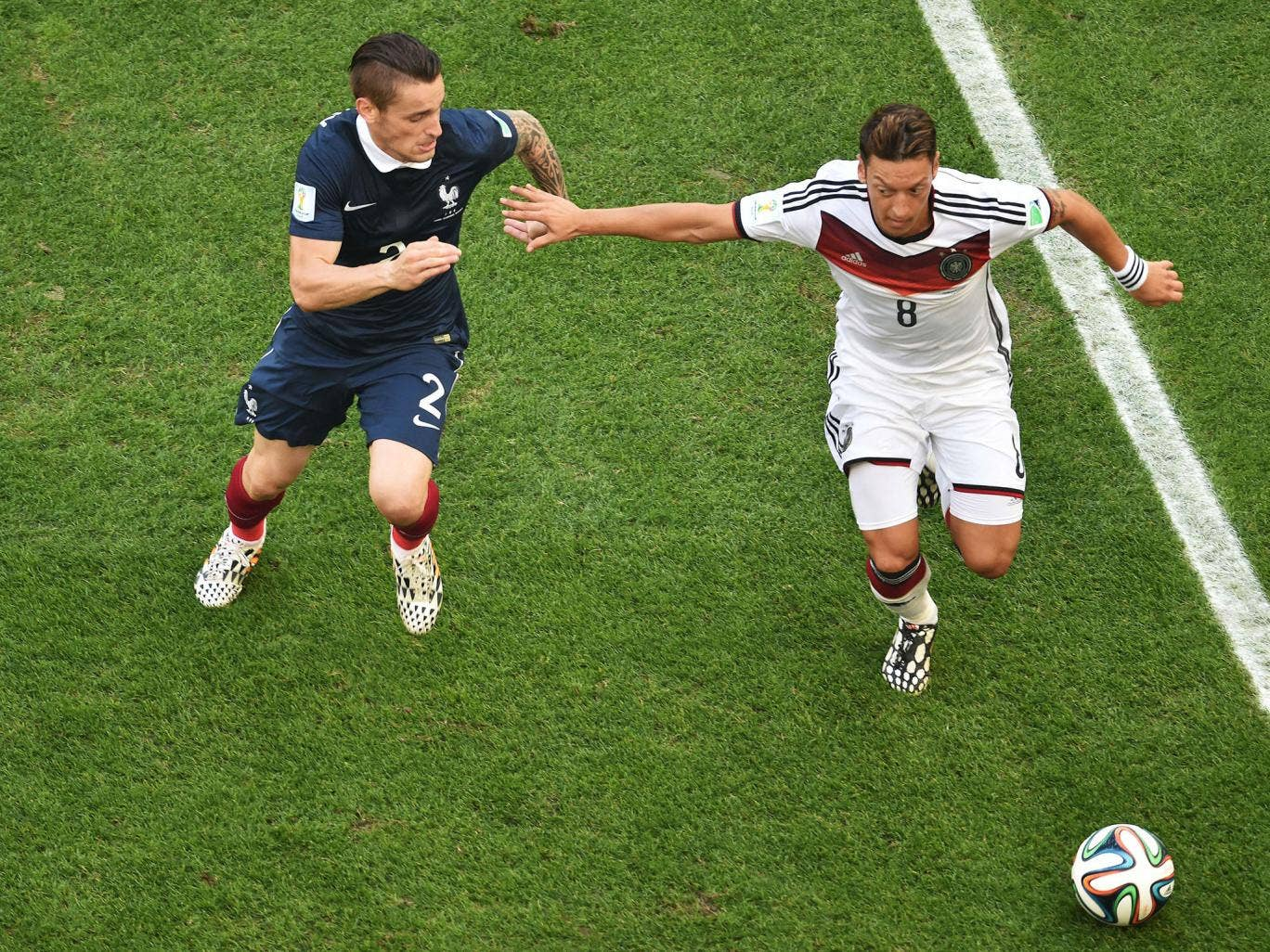 France's defender Mathieu Debuchy (L) tackles Germany's midfielder Mesut Ozil