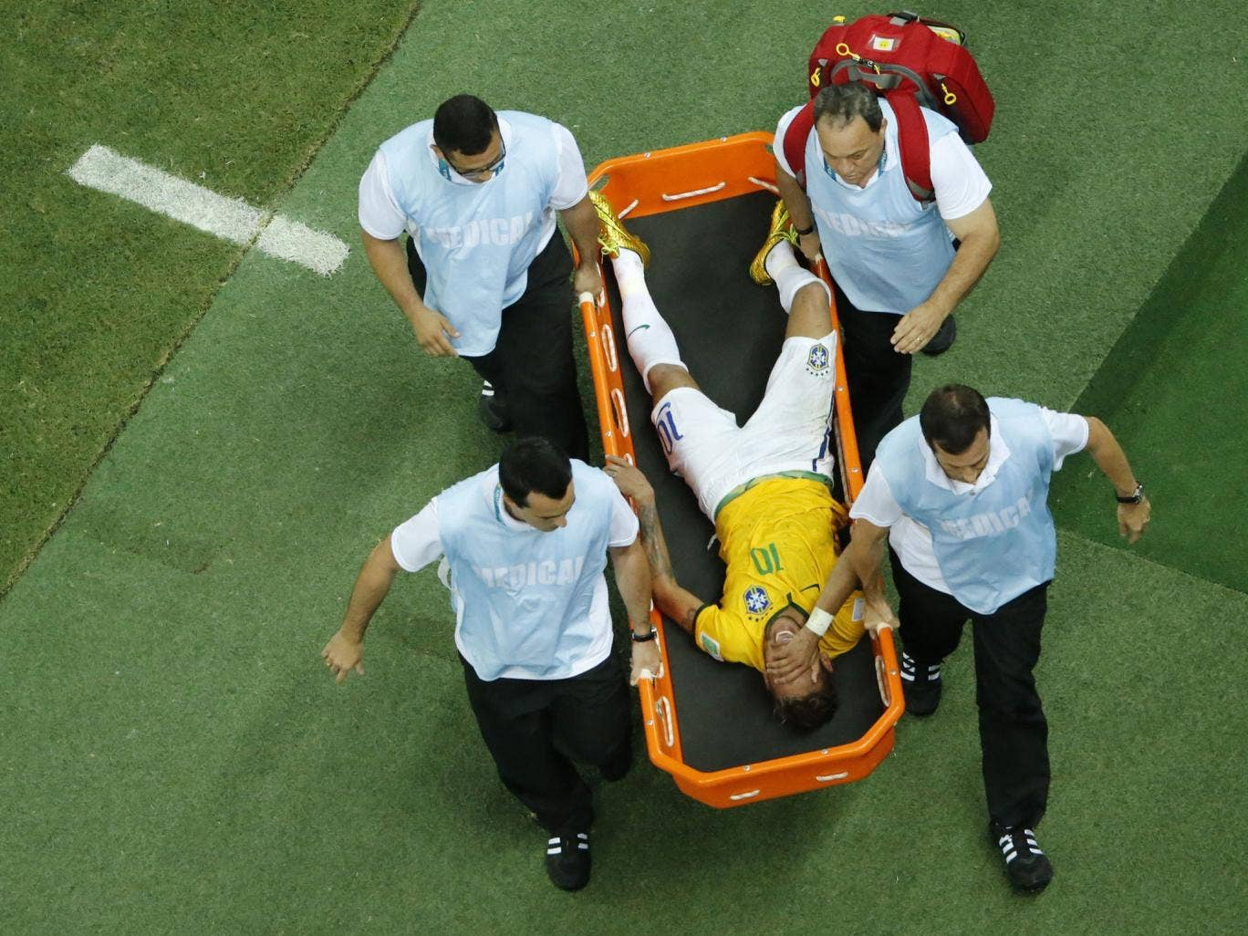 Brazil's forward Neymar is carried on a stretcher after being injured during the quarter-final football match between Brazil and Colombia