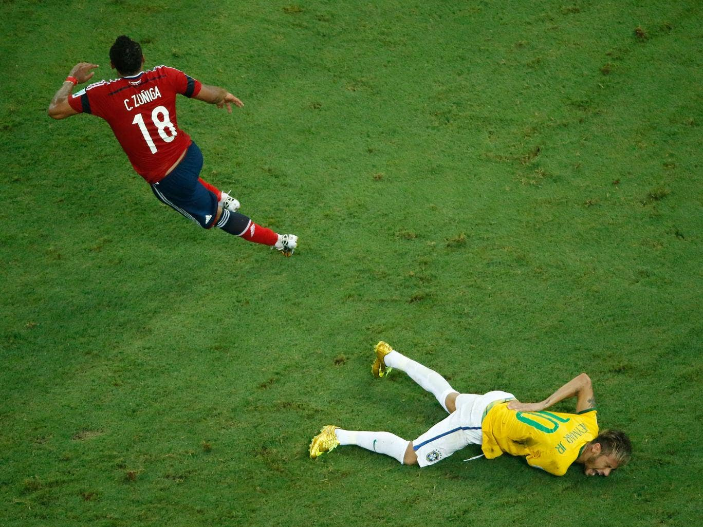 Neymar holds his back after the challenge from Zuniga