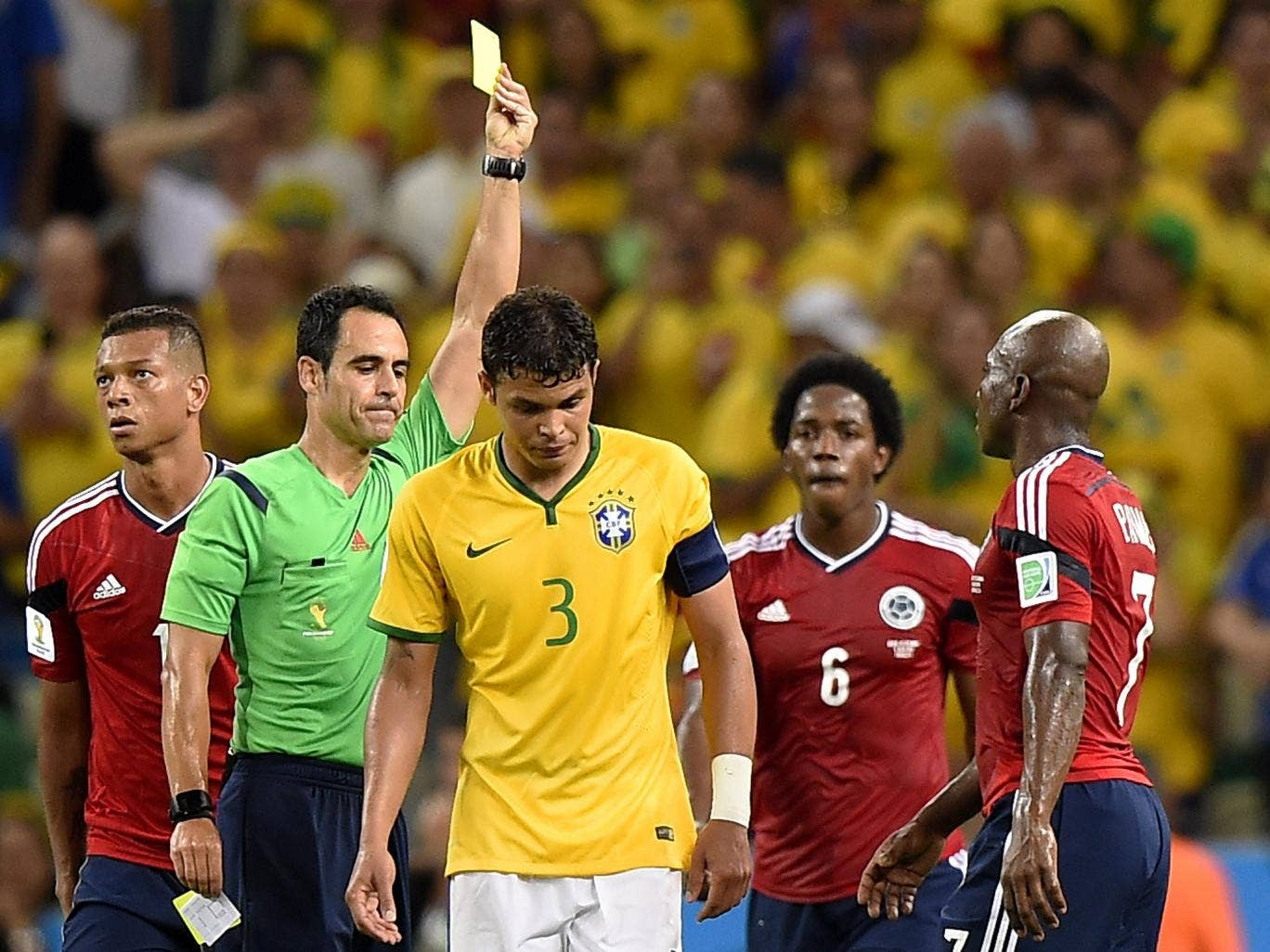 Carlos Velasco Carballo cautions Thiago Silva, a booking that rules the Brazil captain out of the semi-final with Germany