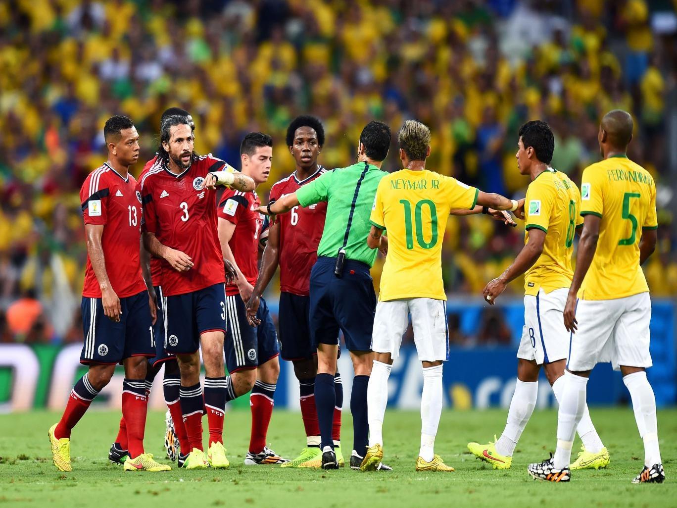 Referee Carlos Velasco Carballo separates Colombia's James Rodriguez and Paulinho of Brazil
