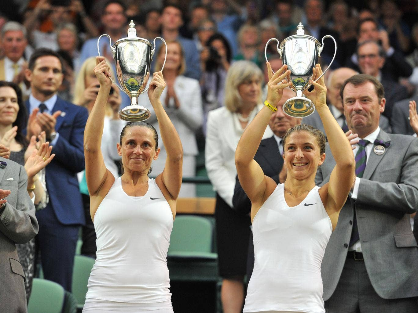 Italy's Sara Errani (R) and Roberta Vinci hold their winners' trophies during the presentation after winning their women's doubles final