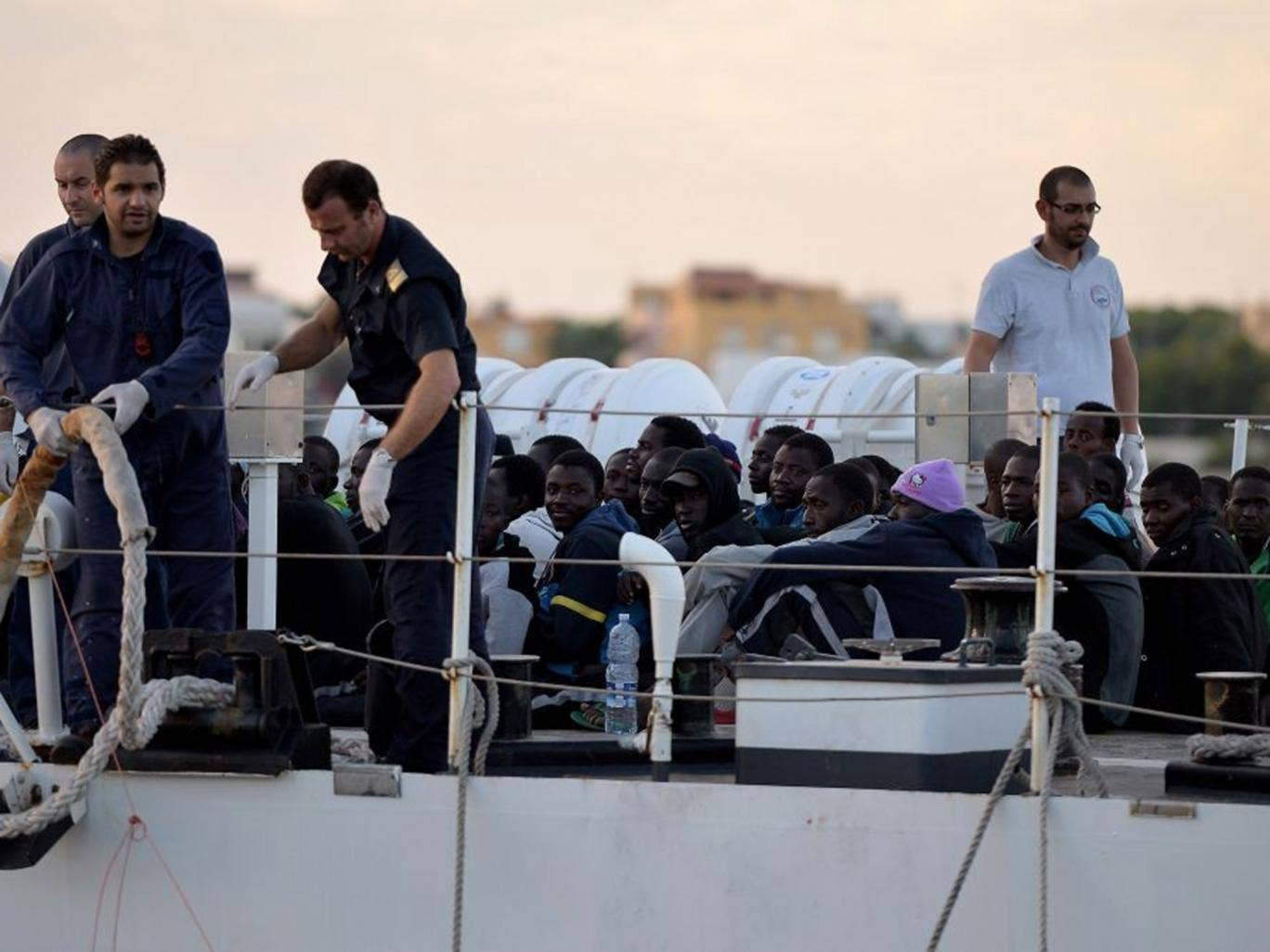 Some 100 migrants sit on the Guardia Costiera boat after being rescued off the shores of the island of Lampedusa last year