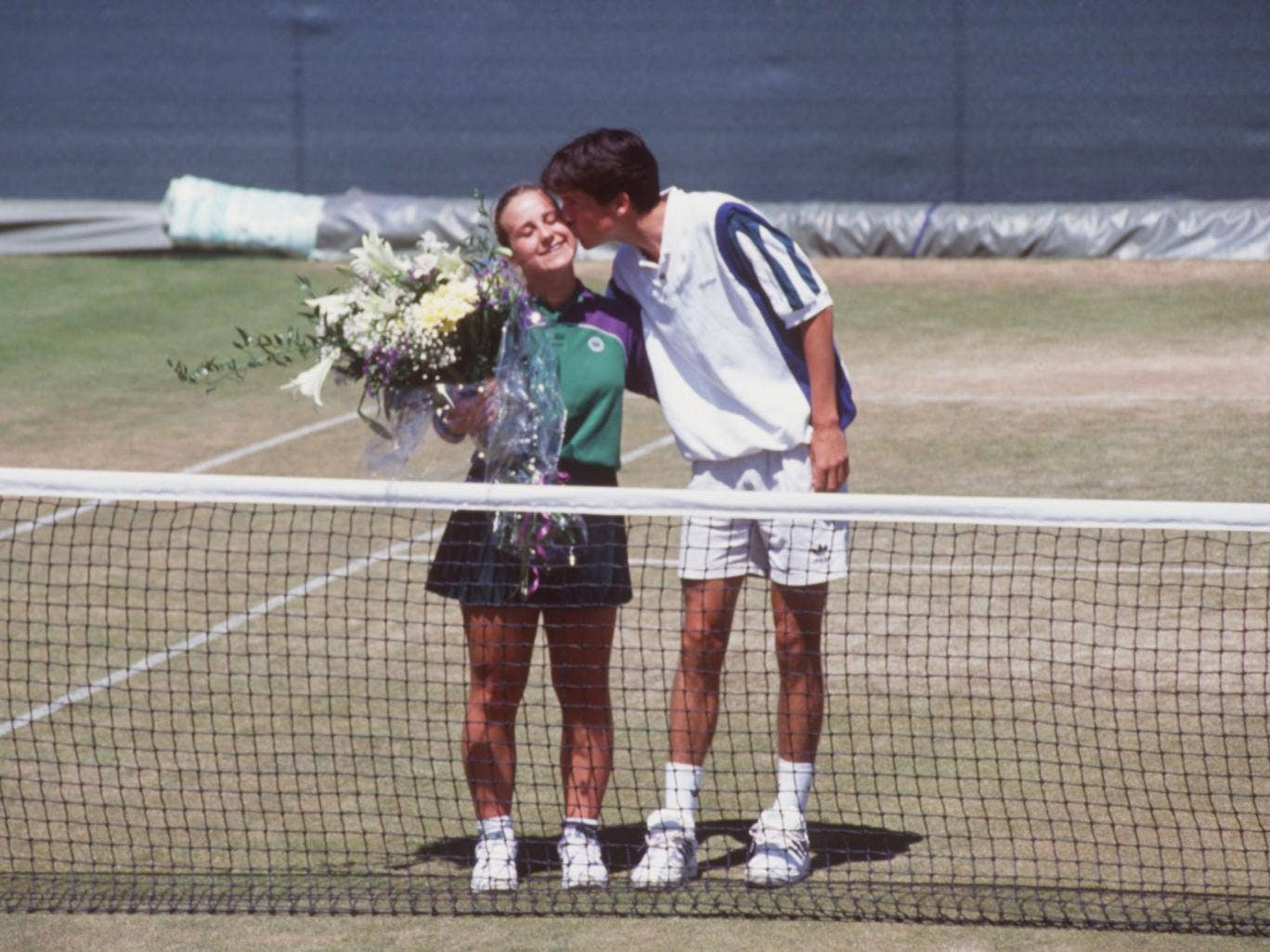 Tim Henman kissing ballgirl Caroline Hall on the cheek a day after he accidentally hit her during a doubles match with Jeremy Bates and was disqualified from the 1995 Wimbledon championships
