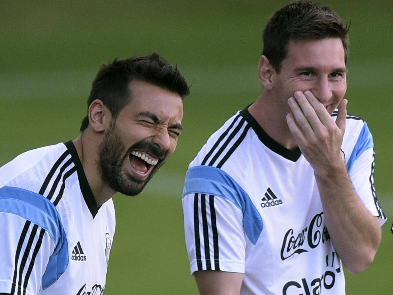 Ezequiel Lavezzi and Lionel Messi share a joke during training