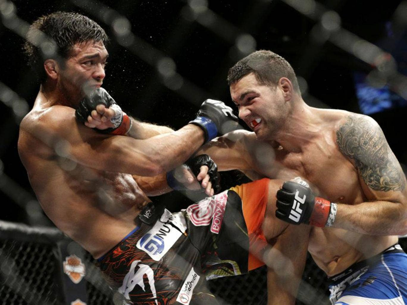 Chris Weidman (right) hits Lyoto Machida during their mixed martial arts middleweight title bout at UFC 175 Saturday