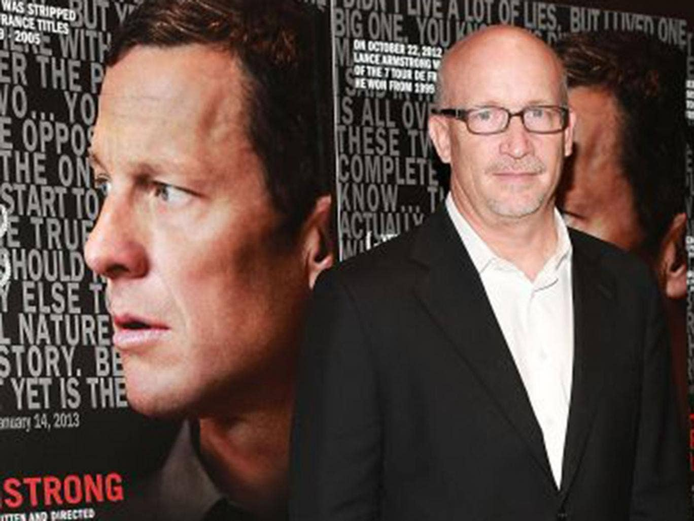 Alex Gibney with posters for 'The Armstrong Lie'
