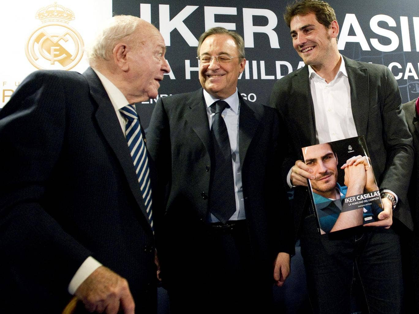 Real Madrid's goalkeeper and captain Iker Casillas (R) poses with his biography 'La humildad del campeon' (The humility of the champion) flanked by President of Real Madrid football club Florentino Perez and President of Honour of Real Madrid Alfredo Di S