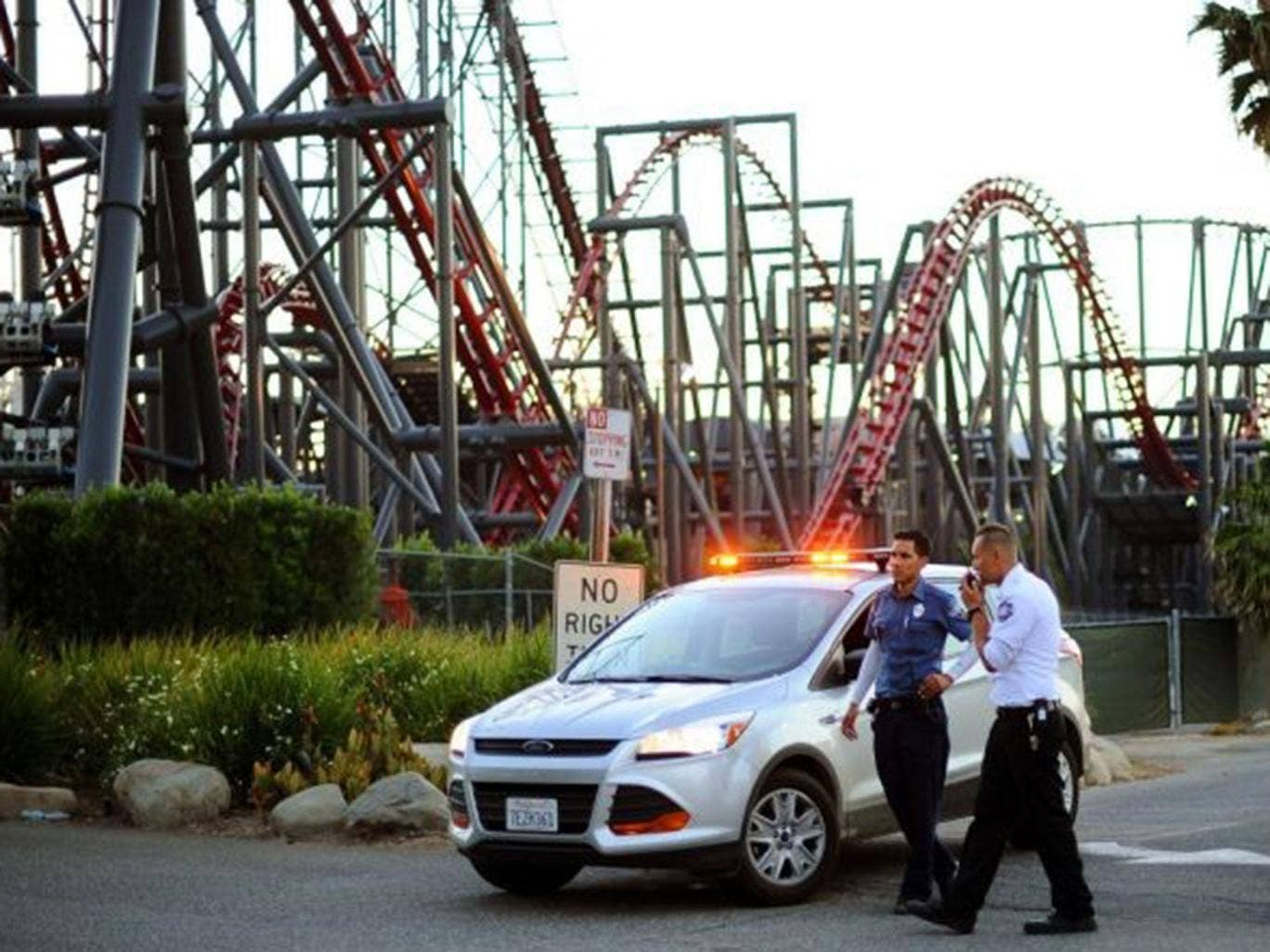 Members of the Six Flags Magic Mountain amusement park security staff monitor the situation at the exit of the park after riders were injured on the Ninja coaster Monday, July 7,