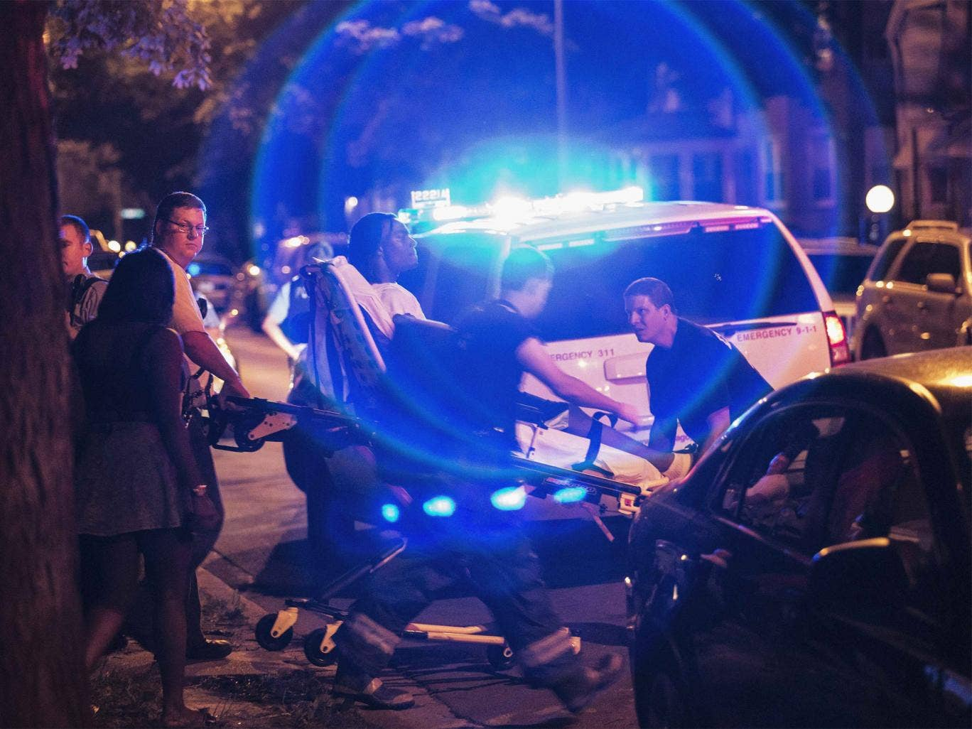 A man is wheeled on a stretcher after being shot in the leg on Chicago's South Side on July 6