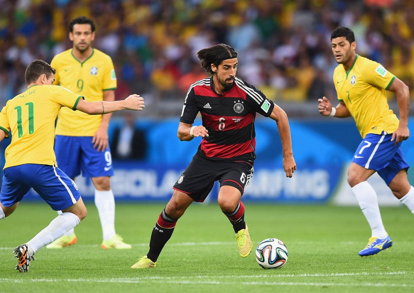 Sami Khedira of Germany runs past Oscar of Brazil with the ball during the 2014 FIFA World Cup Brazil Semi Final match between Brazil and Germany