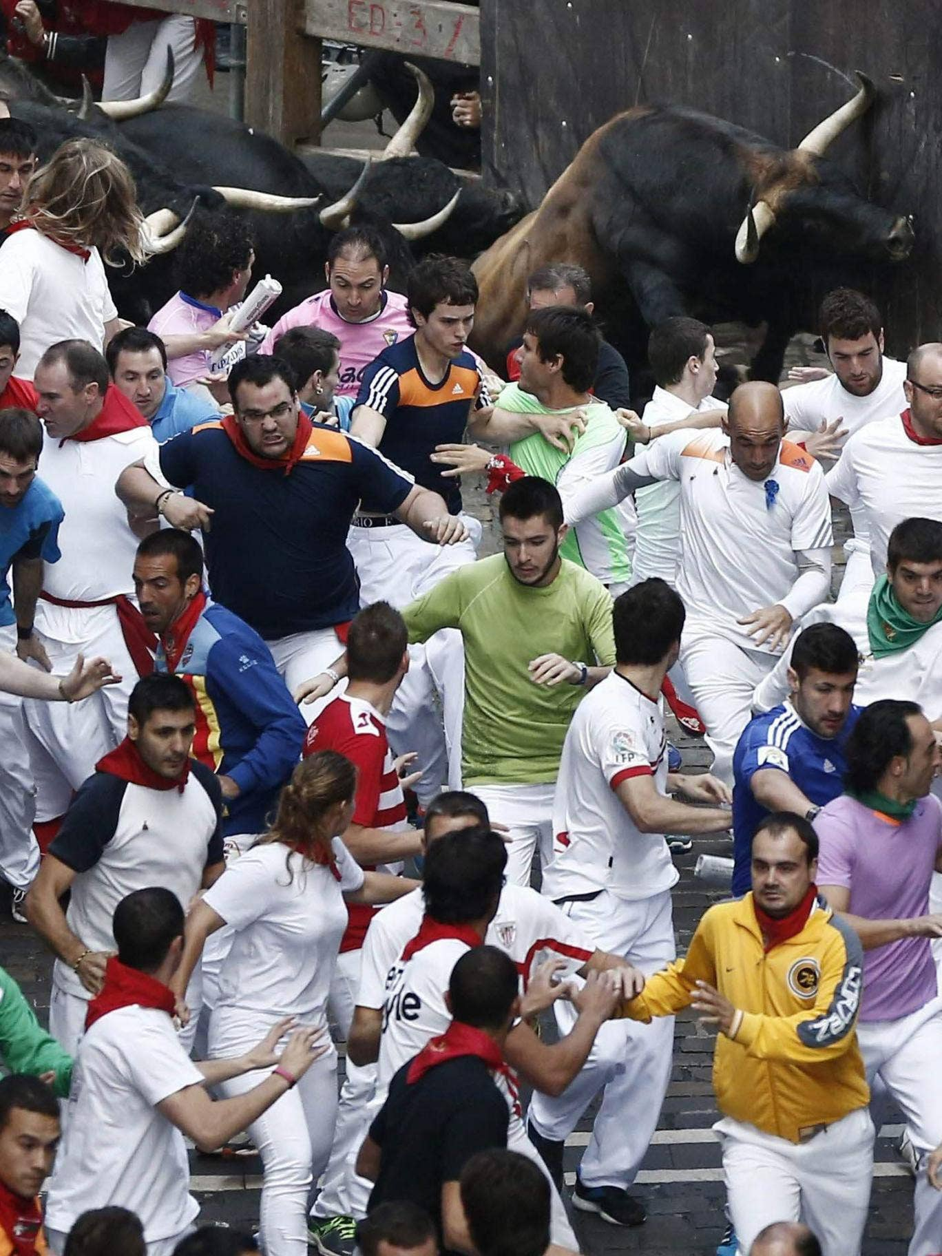 'Mozos' or runners are crowded together as bulls from the 'Jarandilla' ranch turn La Estafeta street during de fifth bullrun at the San Fermin fiestas in Pamplona