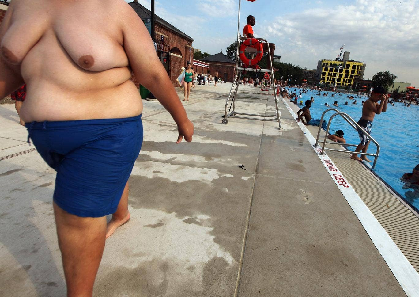 An obese man cools off by a pool