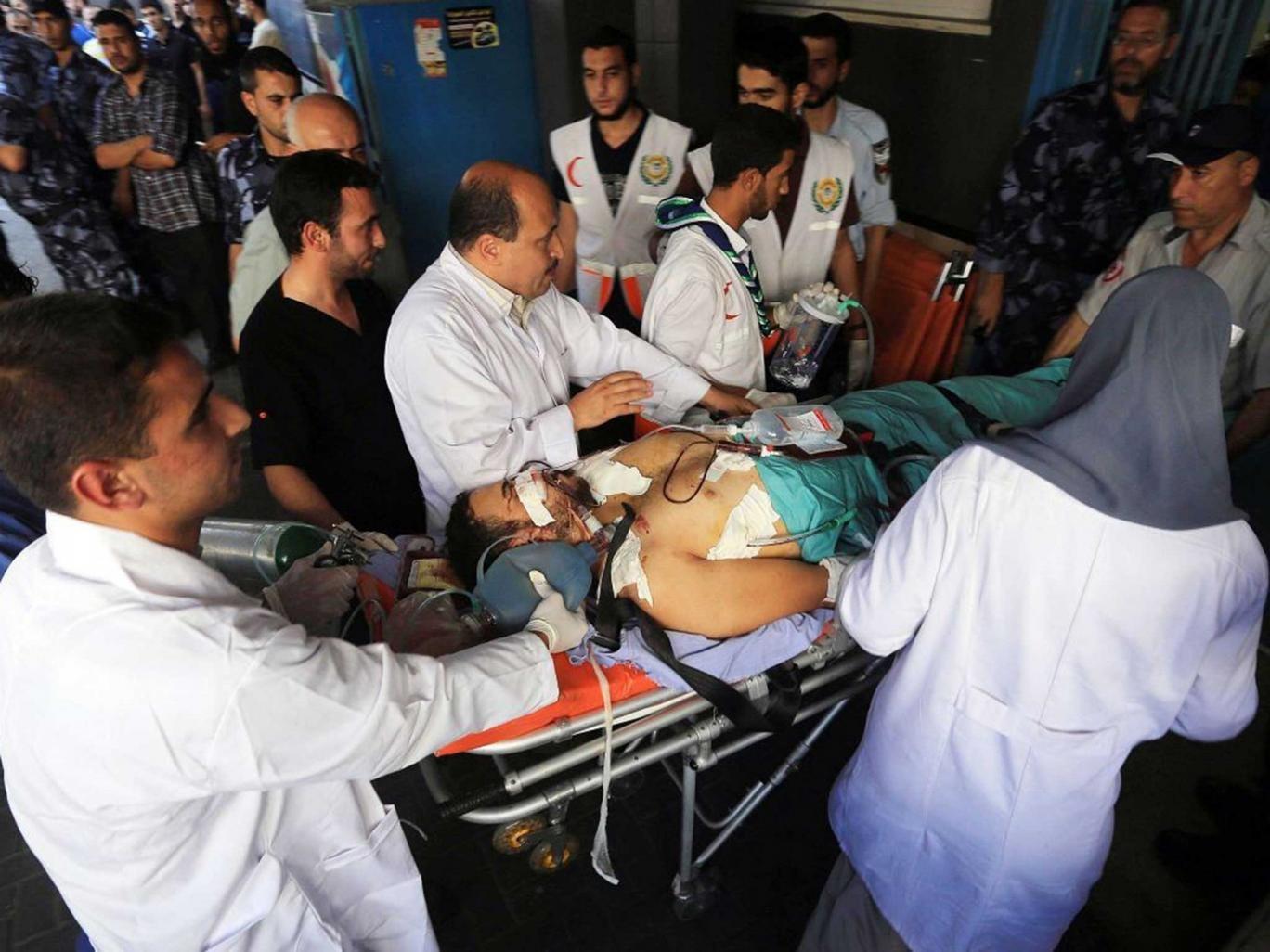 Doctors at Al‑Shifa hospital in Gaza City attempt to treat victims of Israeli air strikes