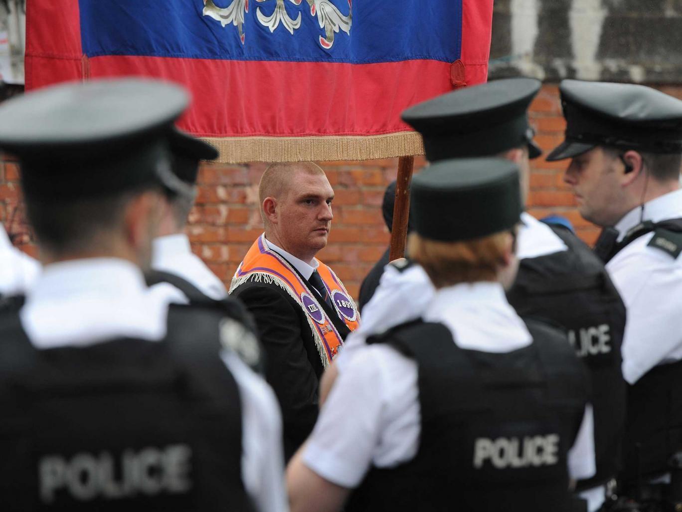 Orangemen march past Ardoyne, watched by police yesterday
