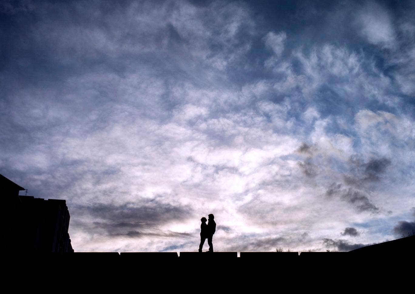 A couple stand in front of a beautiful cloudy scene
