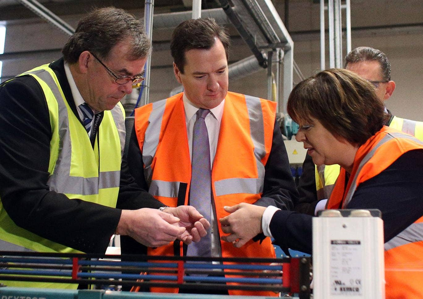 Chancellor George Osborne (C) wears a high visibility jacket as he makes a visit to the Prysmian Group factory and speaks to factory manager Steve Price