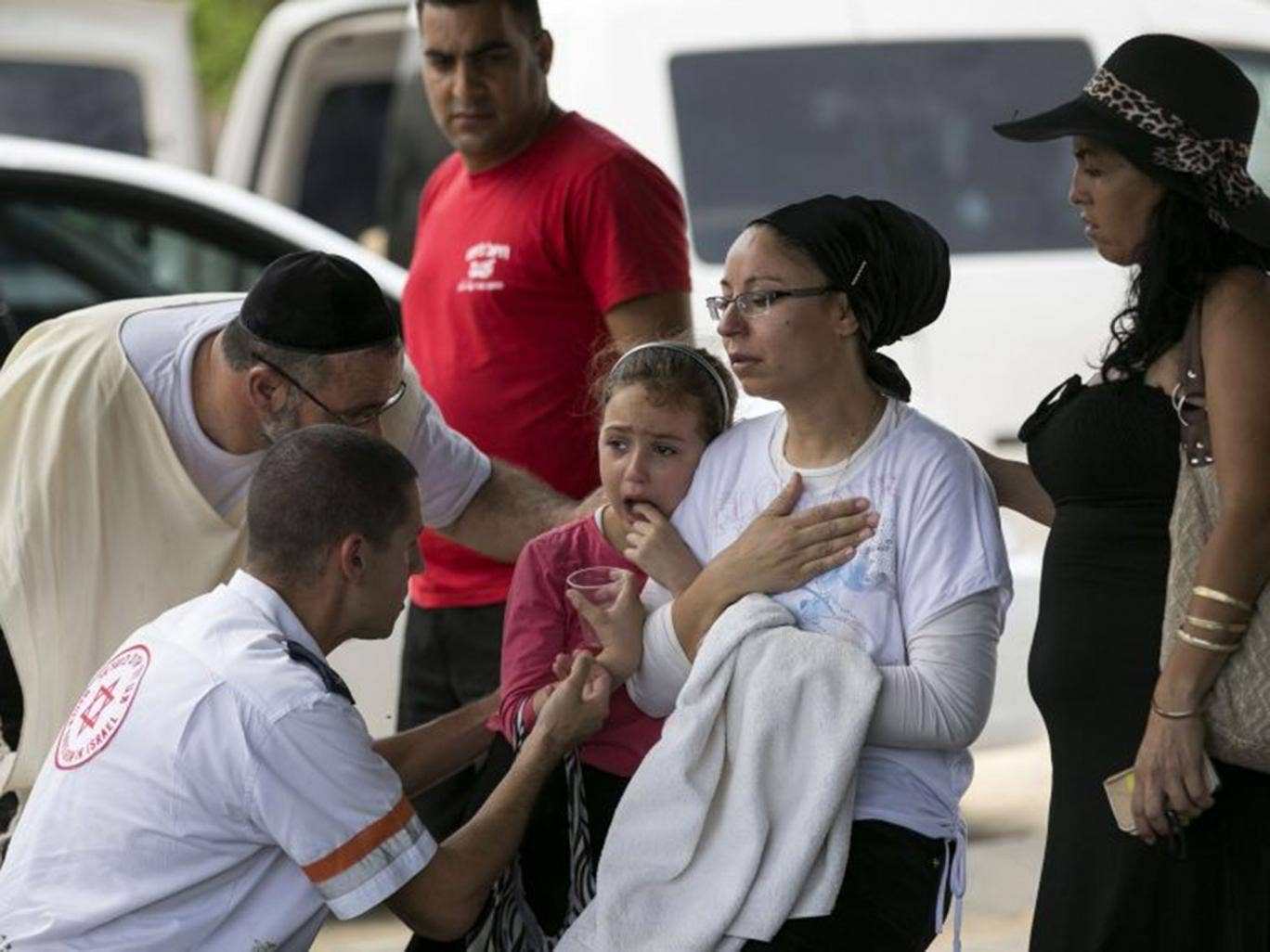 An Israeli mother and daughter are comforted at the scene of a rocket attack in Ashkelon yesterday