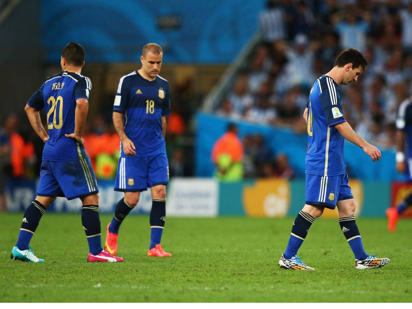Lionel Messi, Sergio Aguero and Rodrigo Palacio trudge after the pitch after the World Cup final