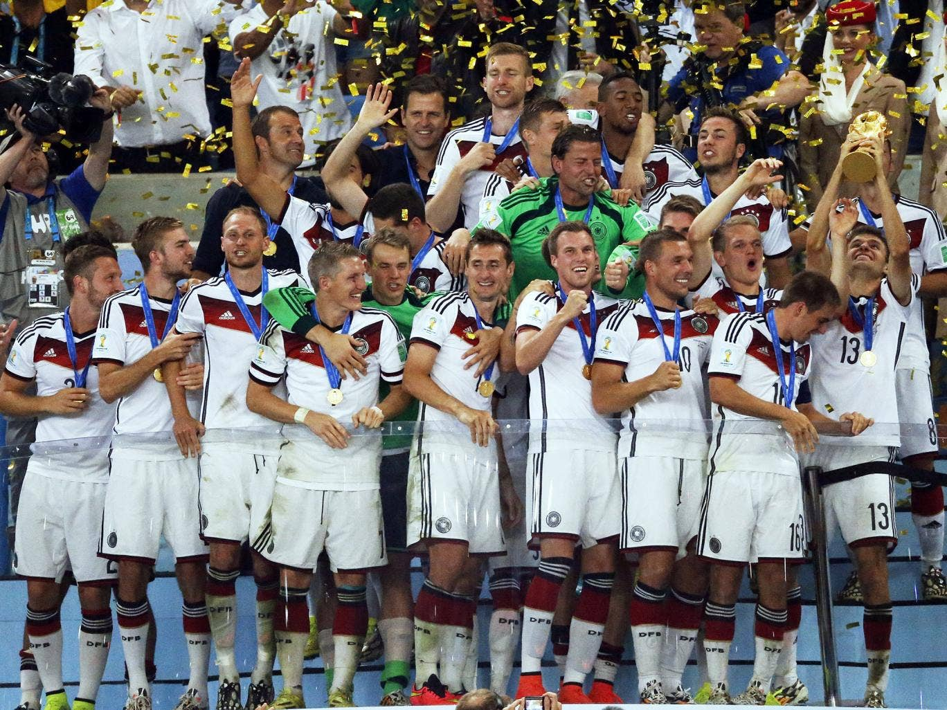 Germany's Thomas Mueller (R) lifts the trophy beside his teammates after the World Cup final soccer match between Germany and Argentina at the Maracana Stadium in Rio de Janeiro, Brazil